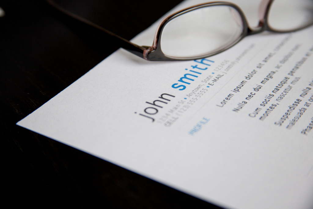 A pair of glasses lying on top of a CV