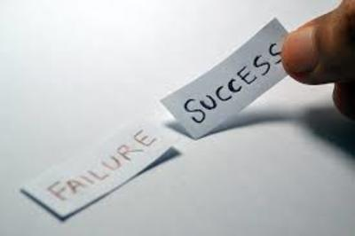 Two pieces of paper with the words Failure & Success written on them