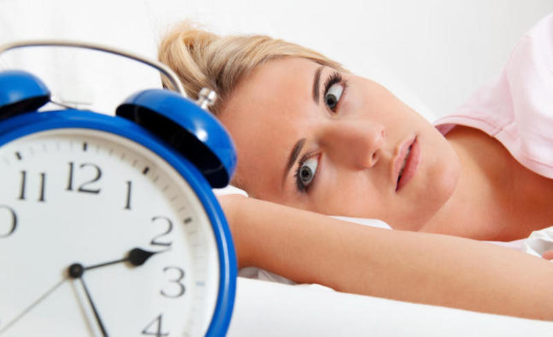 A women in bed with staring at an alarm clock