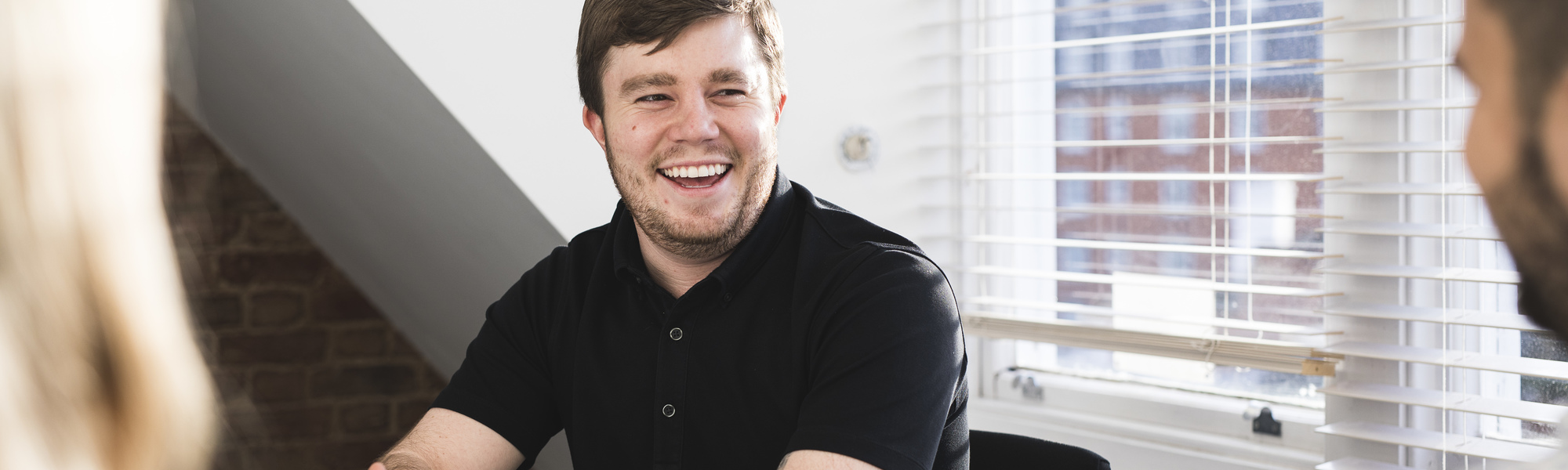 Man in black shirt laughing