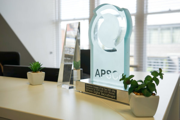 APSCo award sitting on a desk next to a plant
