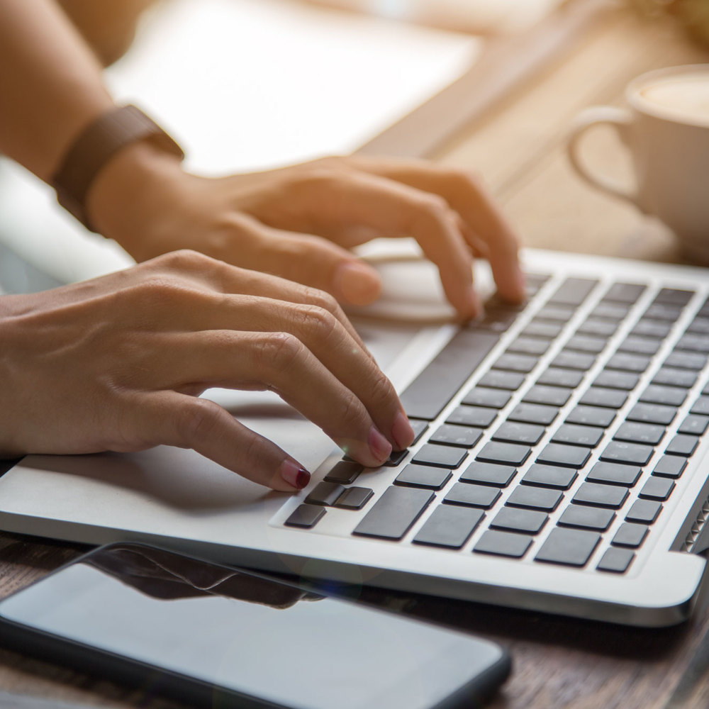 woman hand on her laptop with mobile phone and coffee