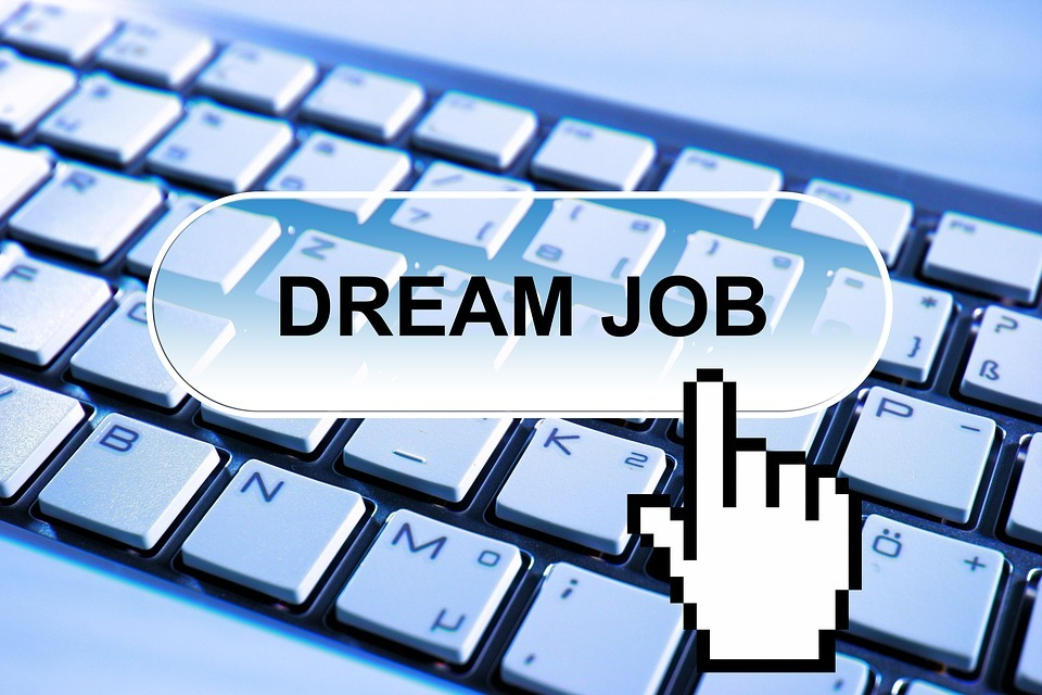Computer keyboard with finger hovering over 'dream job' caption