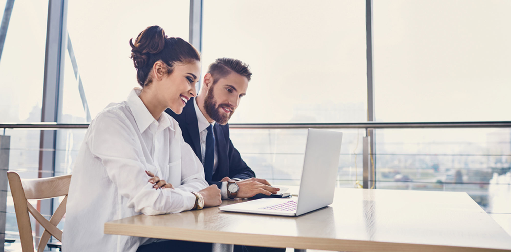 Professional business man and women smiling while working on a laptop