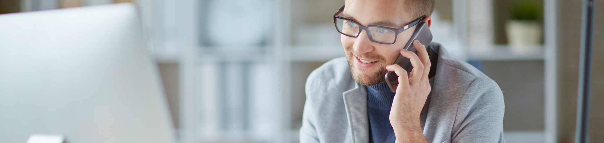 Search Contact Us Header Image. Featuring a brown-haired, bearded, male recruitment consultant wearing glasses and calling back a candidate on his mobile phone as he looks at his desktop. Also featuring a faint office background. Search Consultancy.