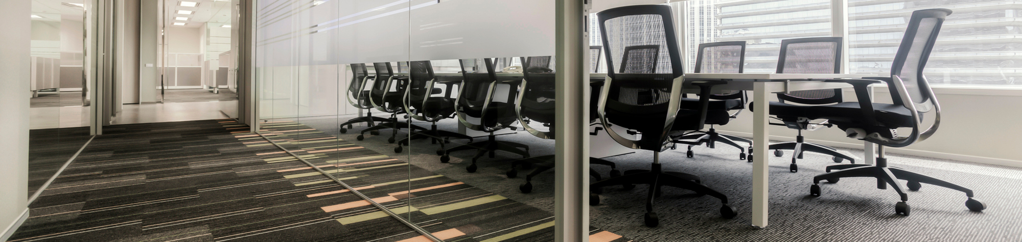 Executive Board Kate McClorey Cover Image. Featuring a glass-walled boardroom with a 14-seater table surrounded by wheeled, grey and black office chairs. Also featuring a square patterned carpet and doorway to another office room. Search Consultancy.