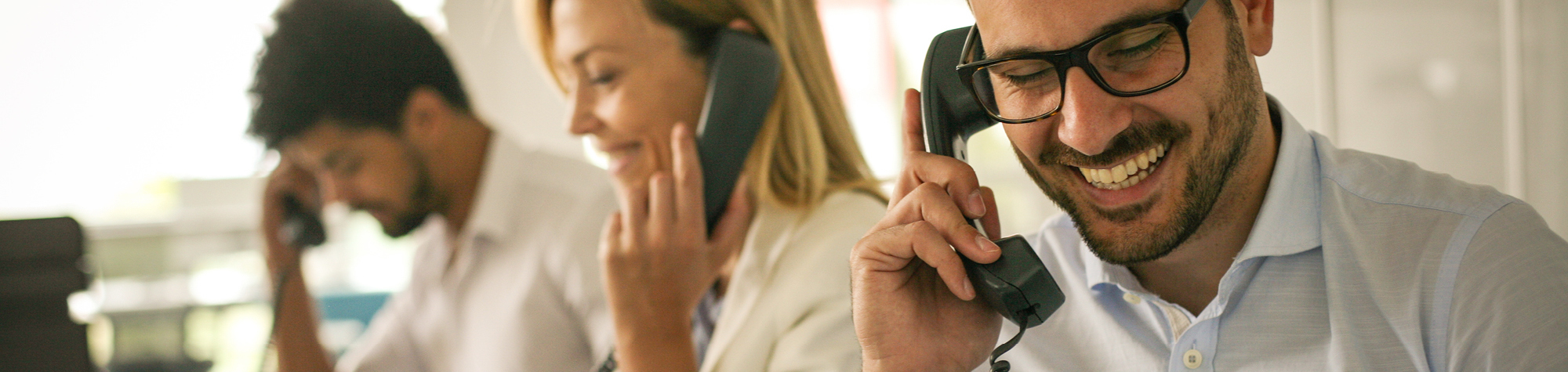 Commercial Discipline Header Image. Featuring male call centre agent speaking on the phone. Also featuring other call centre agents alongside him. Representing exceptional call centre & commercial jobs from Search Consultancy.