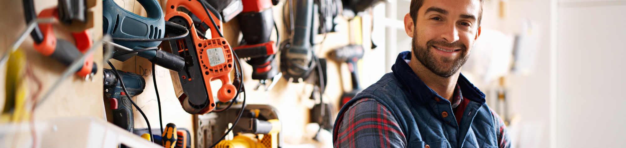 Construction Trades Discipline Header Image. Featuring smiling, male handyman wearing a checked shirt. Also featuring an array of power tools in the background. Representing exceptional construction trades jobs from Search Consultancy.