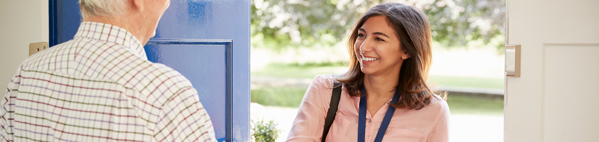 Search Consultancy Healthcare Recruitment Services Header Image Featuring a smiling, female social care professional with brown hair, a pink shirt and blue healthcare lanyard.