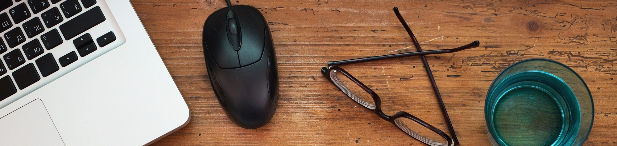 Search Consultancy's Blog Subscription Page. Featuring A Laptop Keyboard, A Mouse, Glasses And A Glass Of Water On A Wooden Desk