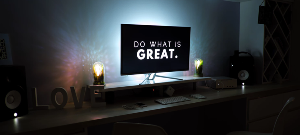 Dark room with computer screen showing a quote Do what is Great.