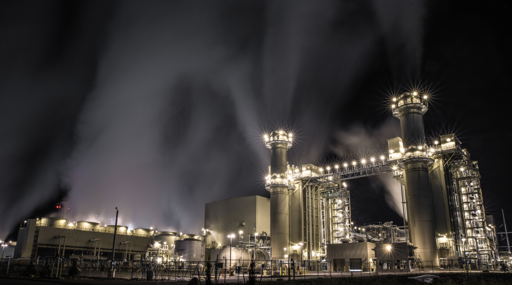 Power Plant at night time with lots of lights and smoke