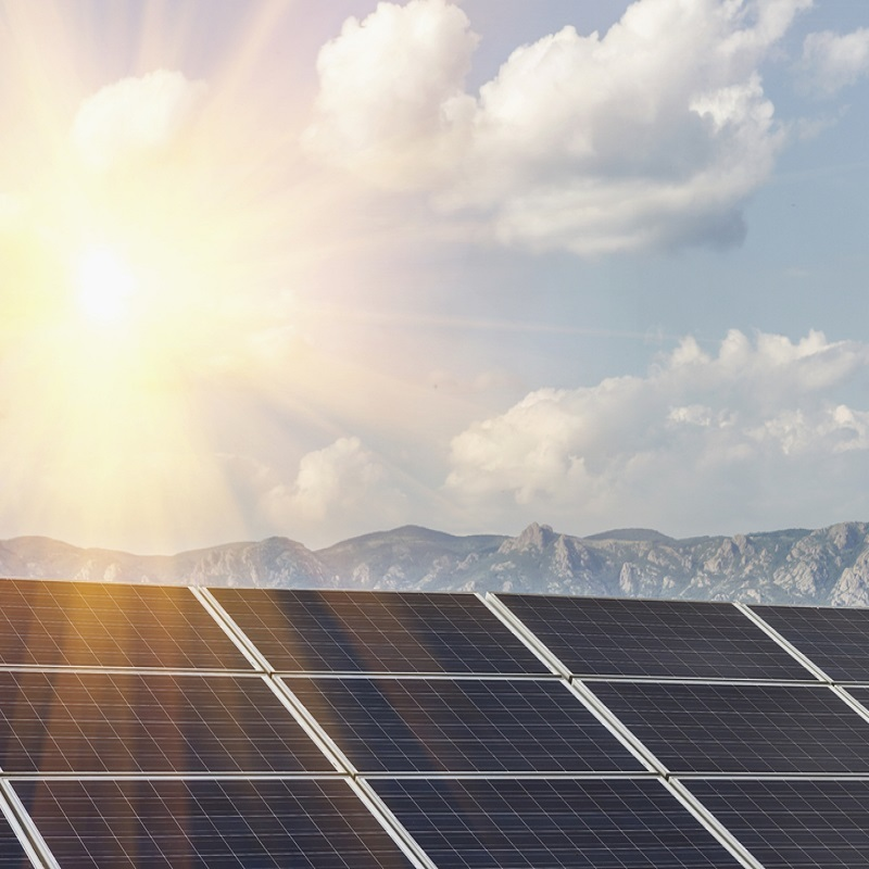 Solar panels with a mountain and bringt sunny background