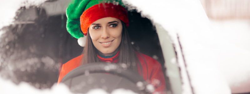 Driving Blog Header Image. Smiling Female Driver Wearing A Christmas Elf Hat And Holding The Steering Wheel Of A Vehicle. Search Consultancy