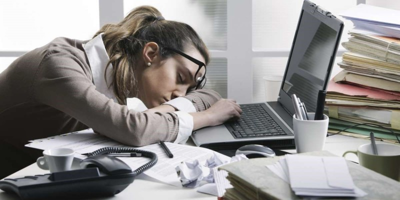 A tired person next to a laptop