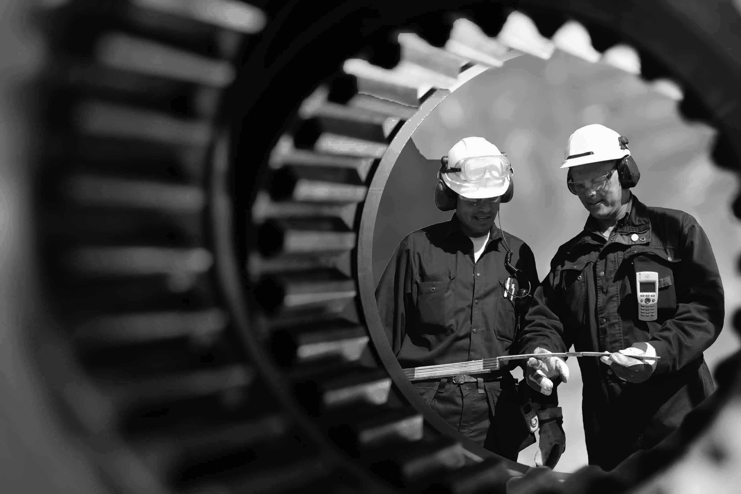 A black and white photo of two energy workers with hard hats