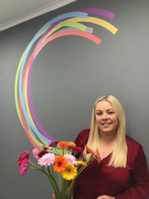 Paige of Compass Point receiving flowers from happy Administration candidate