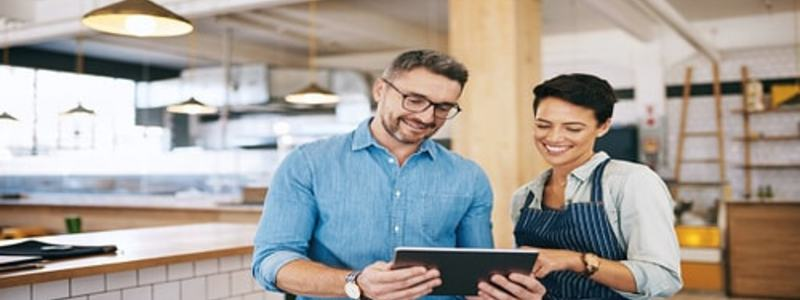 Hospitality Blog Header Image. Featuring Male Restaurant Manager Looking At Menu Options On a Tablet Along With Smiling Female Head Chef. Search Consultancy