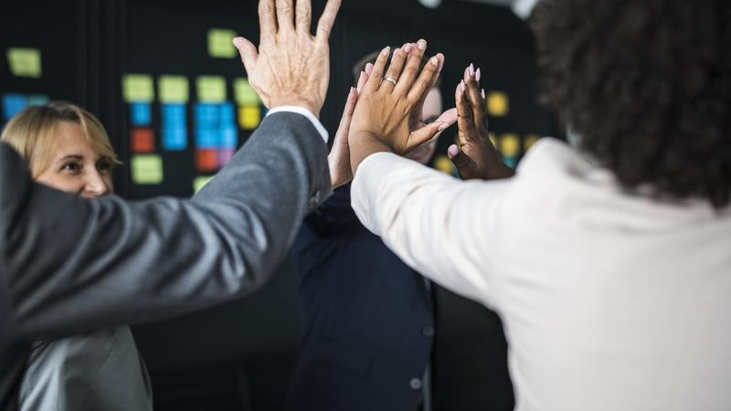 Happy Employees High-Fiving In The Office - Entech Technical Solutions