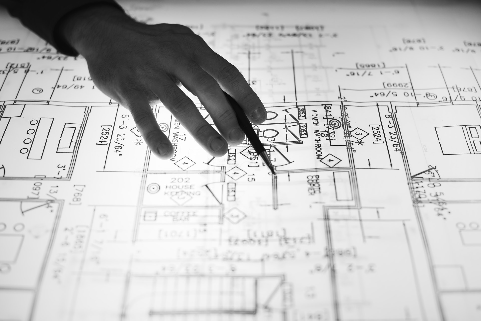 A Surveyor Looking Over Building Plans - Surveyors - The 14 Best Engineering Jobs For The Future