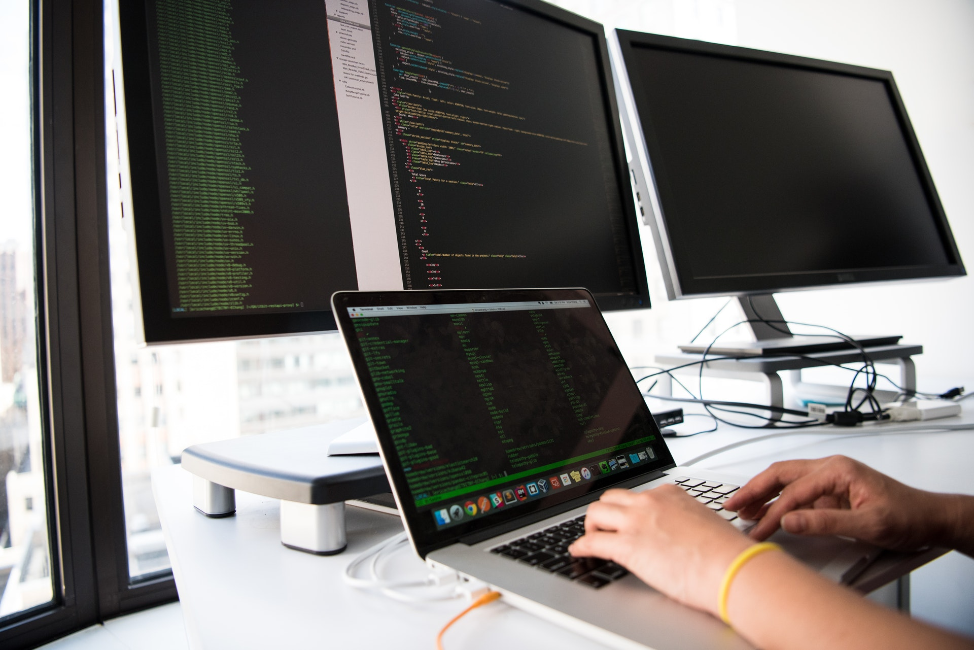 A Computer or Information Research Scientist Analysing And Writing Code On A Computer - The 14 Best Engineering Jobs For The Future