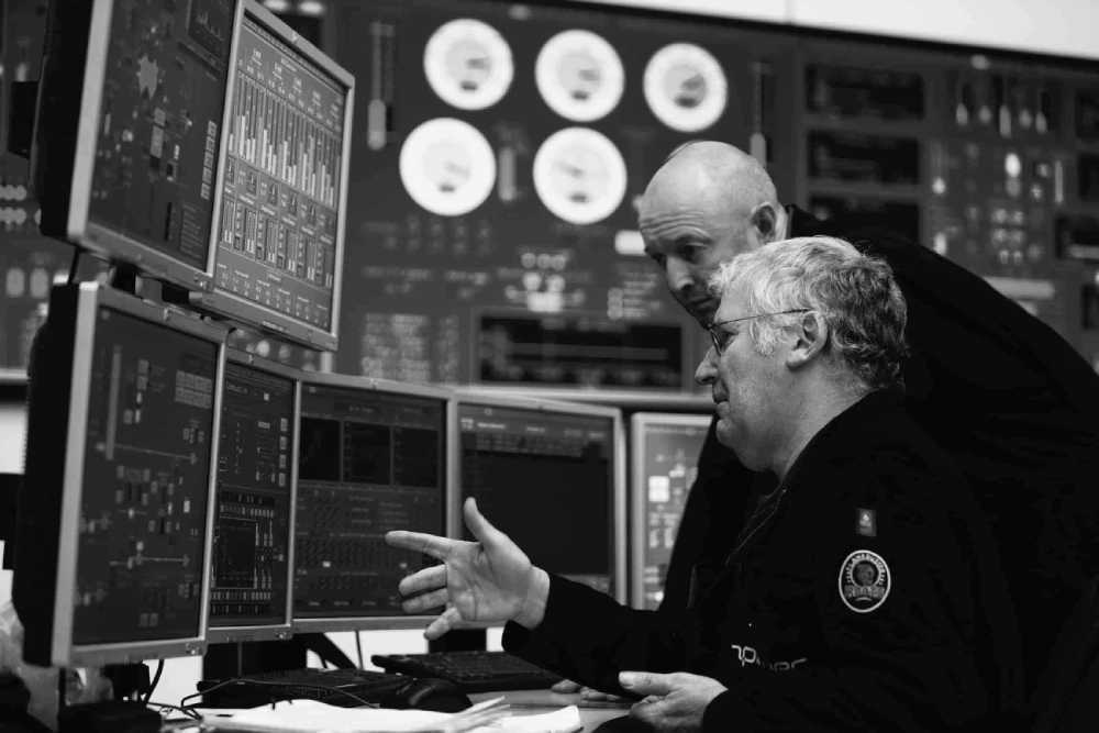A photo of two men in a power station control room