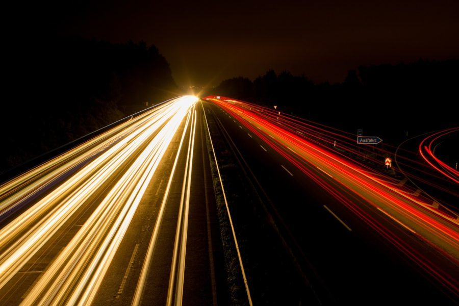 busy highway with timelapse car headlights as they travel up and down the motorway