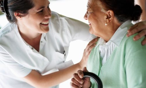 Healthcare worker with eldery woman in care home