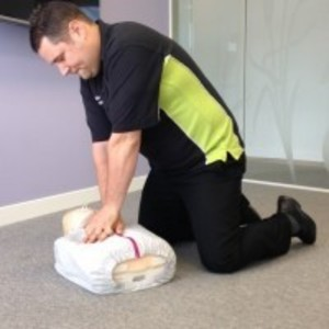 Trainer demonstrating CPR during Emergency first aid at work training with Swanstaff