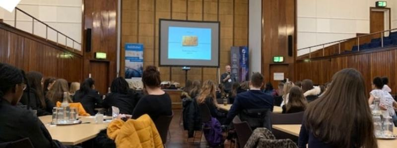 News Article Header Image. Cyber Girls First Event Hosted By Search Consultancy In Manchester. Featuring Schoolgirls Viewing Presentation On Projector As Male Speaker Talks.