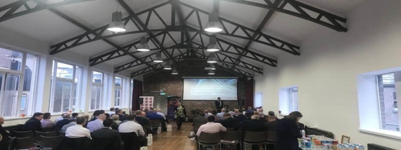 Search News Header Image. Photo Of Transport Crisis Management Seminar. Featuring Attendees Viewing A Presentation On A Projector Screen And A Male Speaker.
