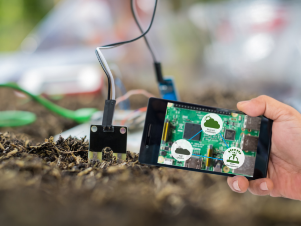 Smart farmer holding smart phone with agritech icons and messages on screen with soil sensor to manage water, soil quality and monitor weather. - Image