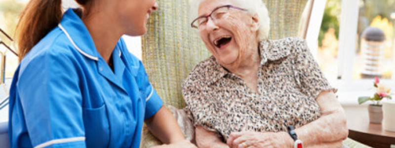 Nursing Blog Header Image. Featuring Female Nurse Smiling At Laughing, Elderly Patient. Search Consultancy