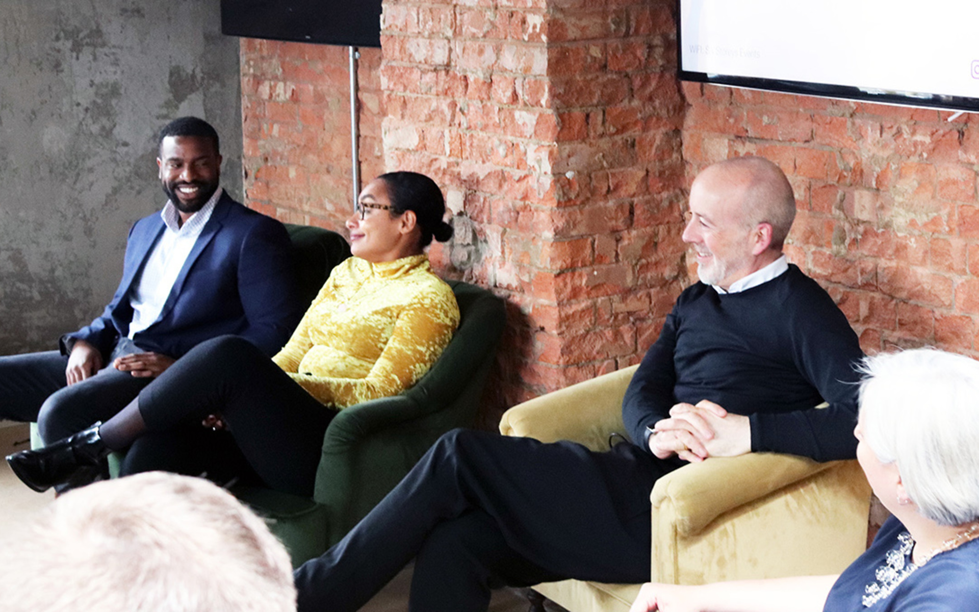 A man in a suit, a women in a yellow top and man in a black jumper on stage at an event in front of a brick wall