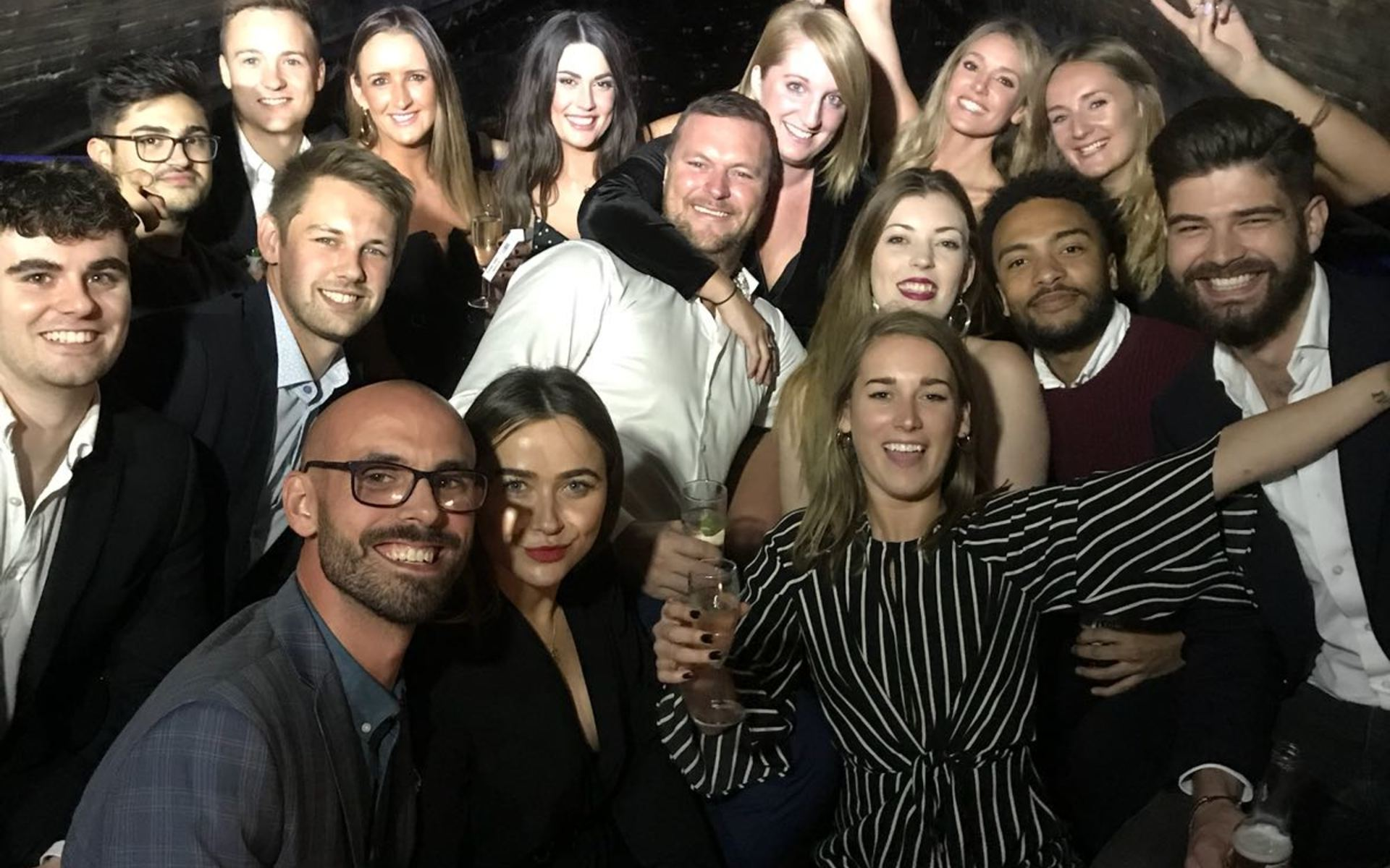 A group of men and women at a party smiling for the camera