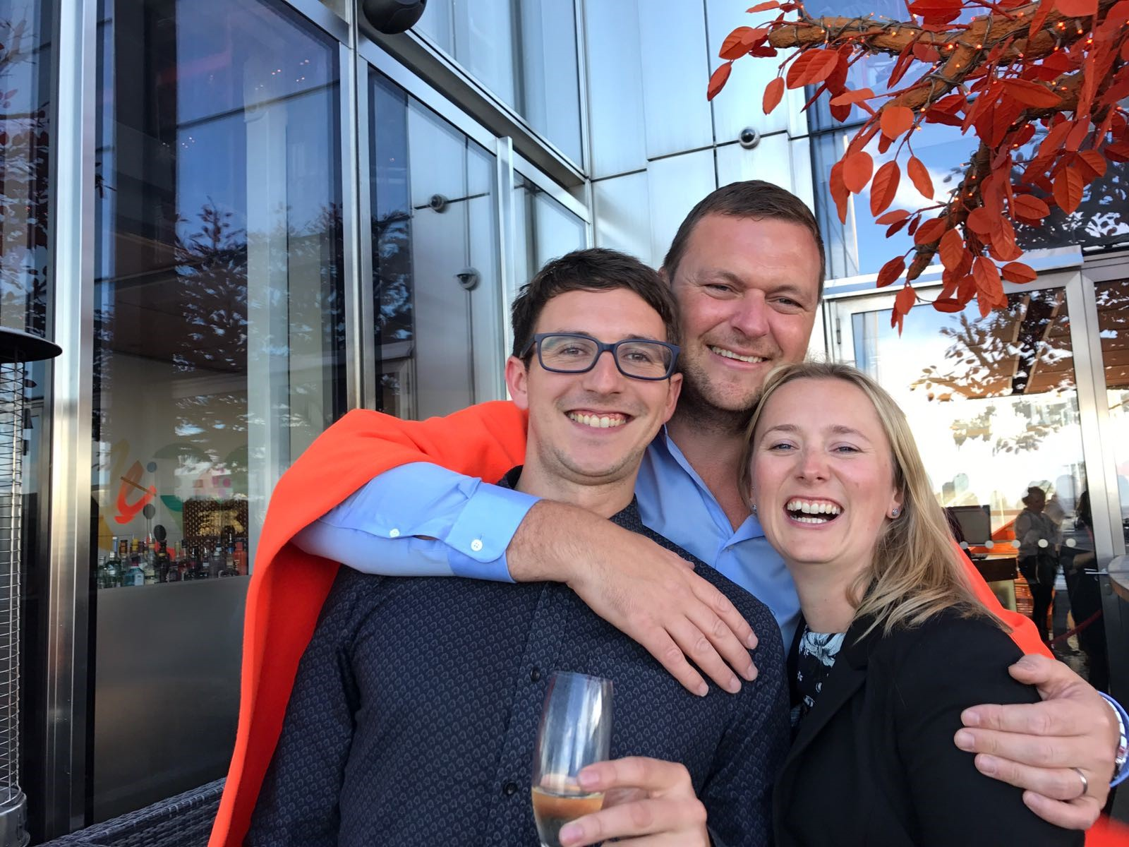 Two men and a women at Sushi Samba smiling with a glass of champagne in their hands