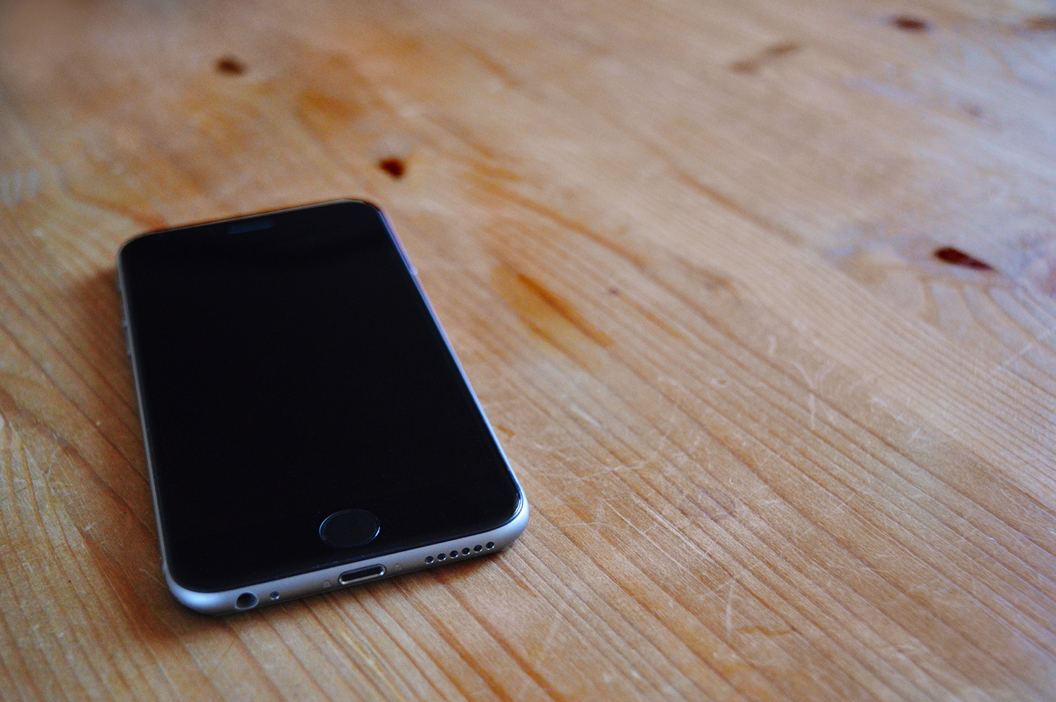 An iPhone on a wooden table
