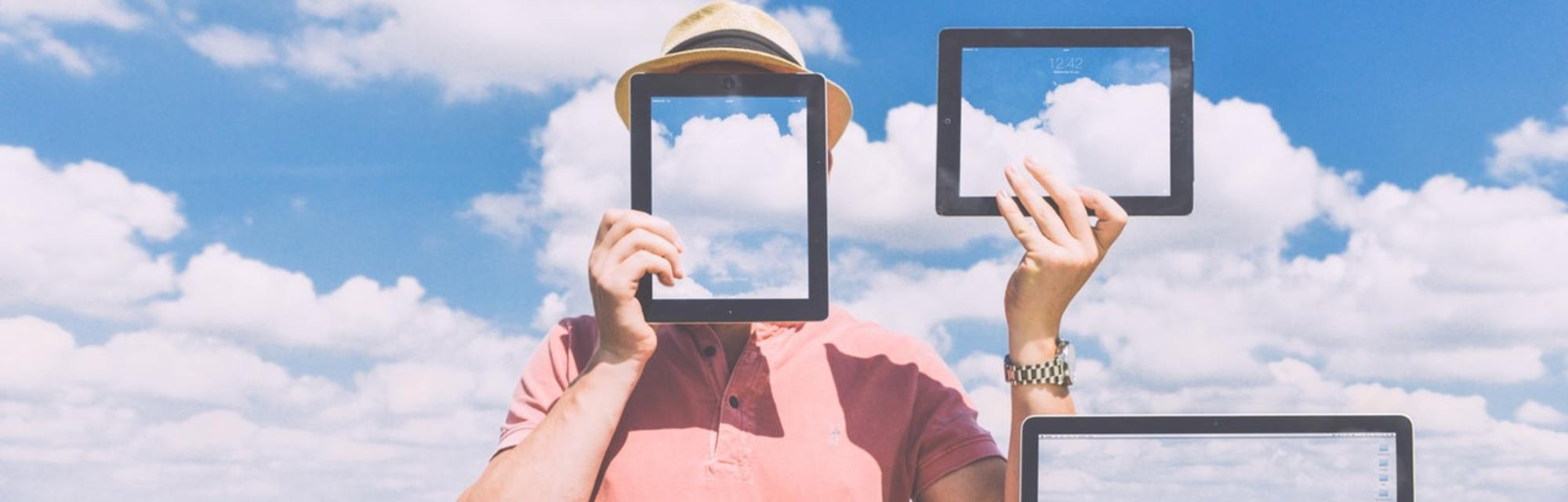 Developer holding ipads with clouds