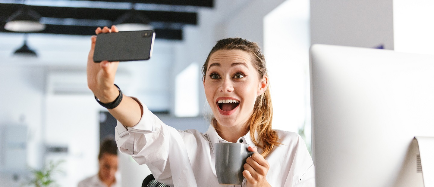 Professional business women taking a selfie at her desk at work