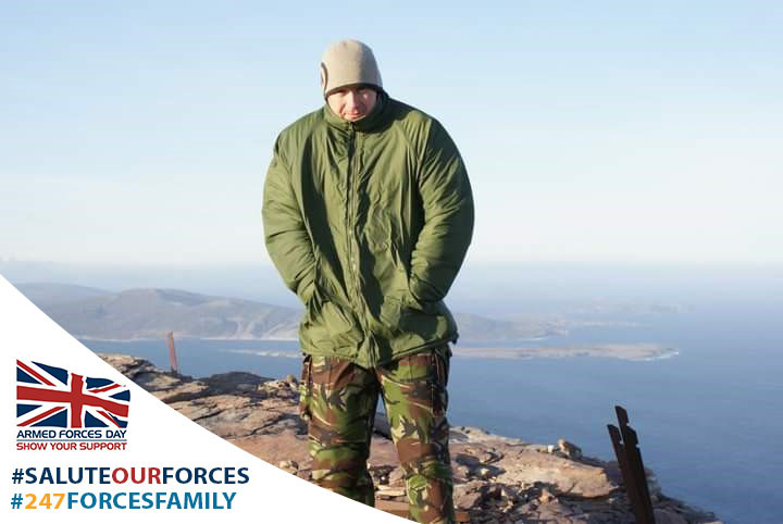 Dean stood on top of a mountain in Armed Forces uniform