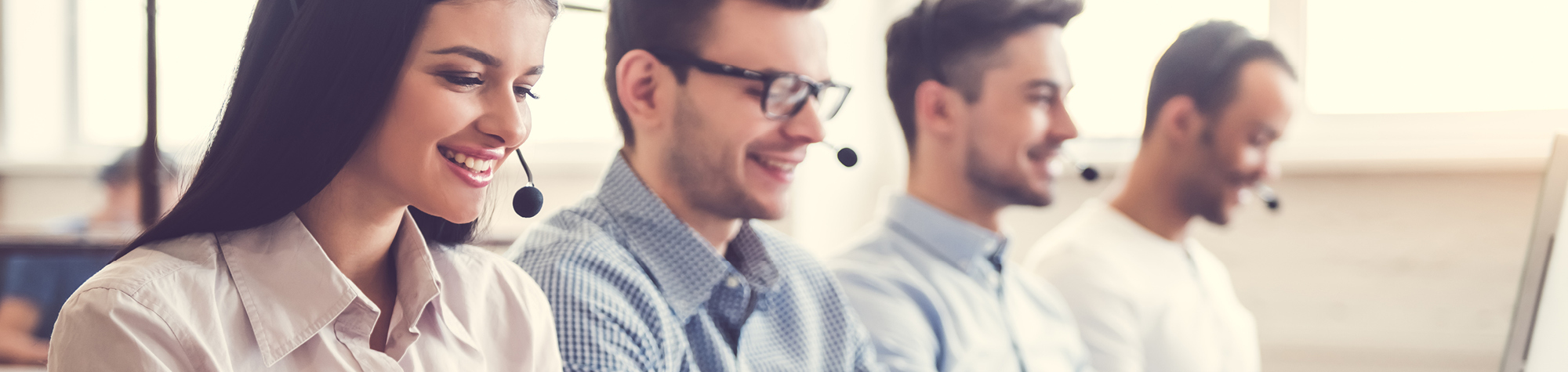 Search Consultancy Call Centre Jobs In Manchester Header Image. Female Call Centre Agent Wearing A Call Centre Headset Smiling In A Busy Call Centre Featuring Three Males Also Wearing Call Centre Headsets.