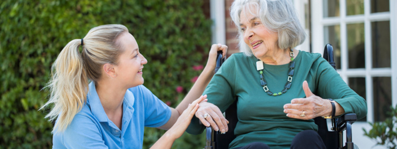 Health & Social Care Blog Header Image. Featuring Smiling Female Care Assistant Listening To Smiling, Elderly, Female Patient In a Wheel Chair. Background Of Garden Bushes And Glass Doors. Search Consultancy.
