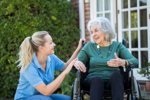 health care assistant talking to a lady in a wheelchair.