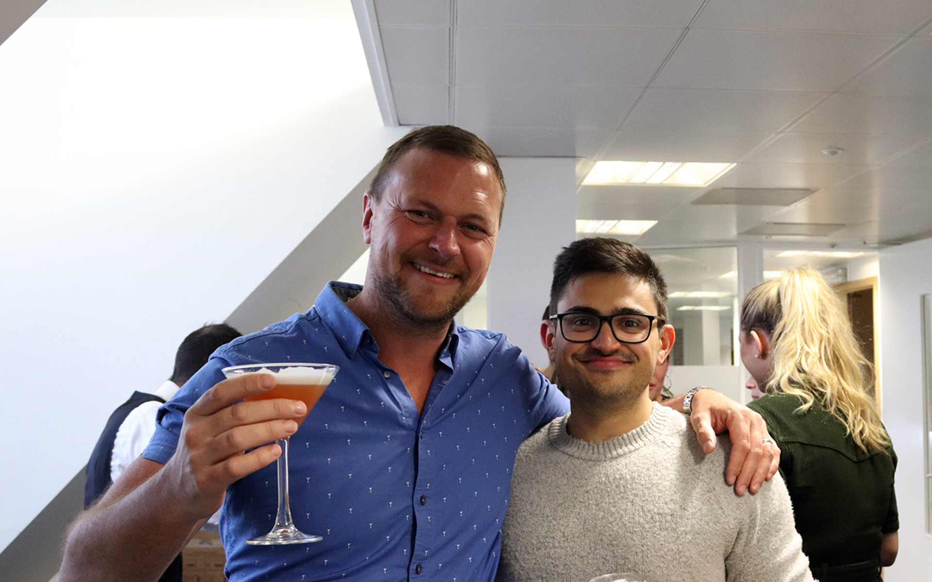 Two men holding cocktails