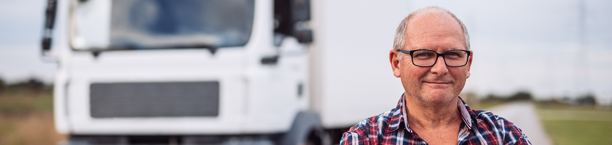 Search Consultancy driving jobs header image. Featuring a male driver smiling in front of a HGV.