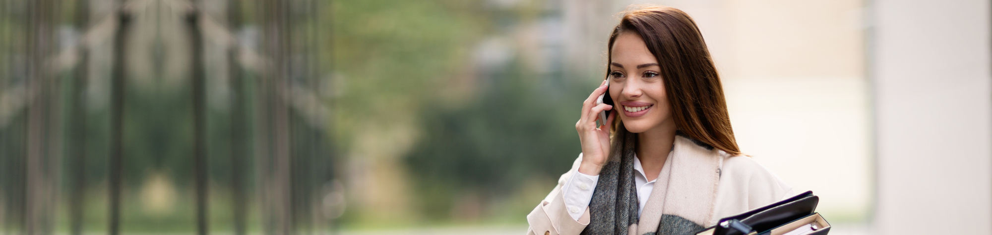 Search Consultancy's Sales Jobs Header Image, featuring smiling sales executive on the phone to a client.