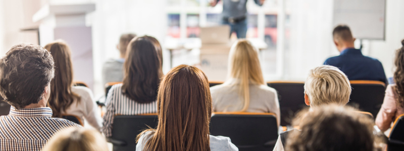 Search Legal News Article Header Image. Featuring Mixed Group Of Male And Female Attendees Viewing A Male Speaker As He Delivers HR Presentation.