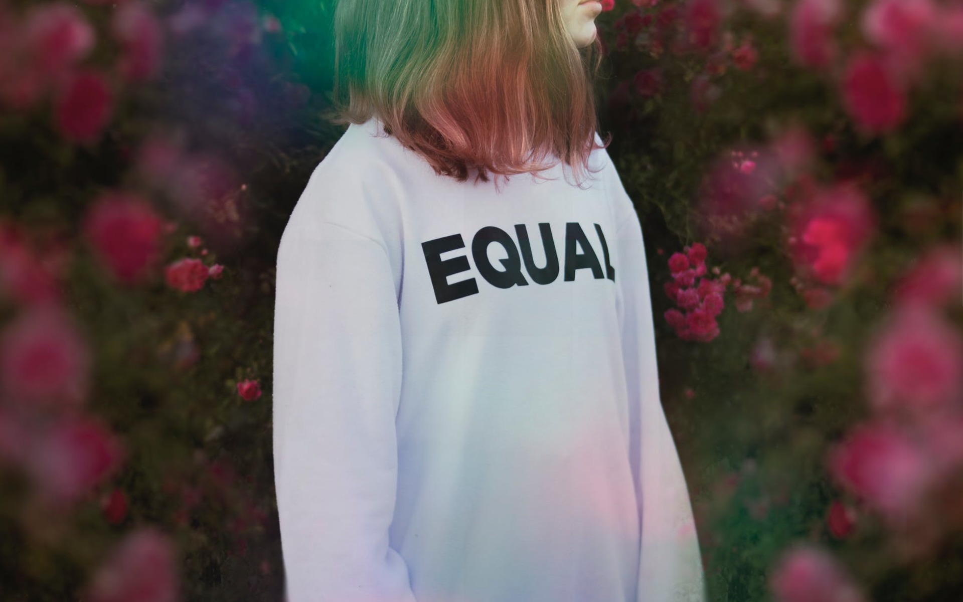 A woman standing in front of a flower wall wearing a white jumper with the words equal on it