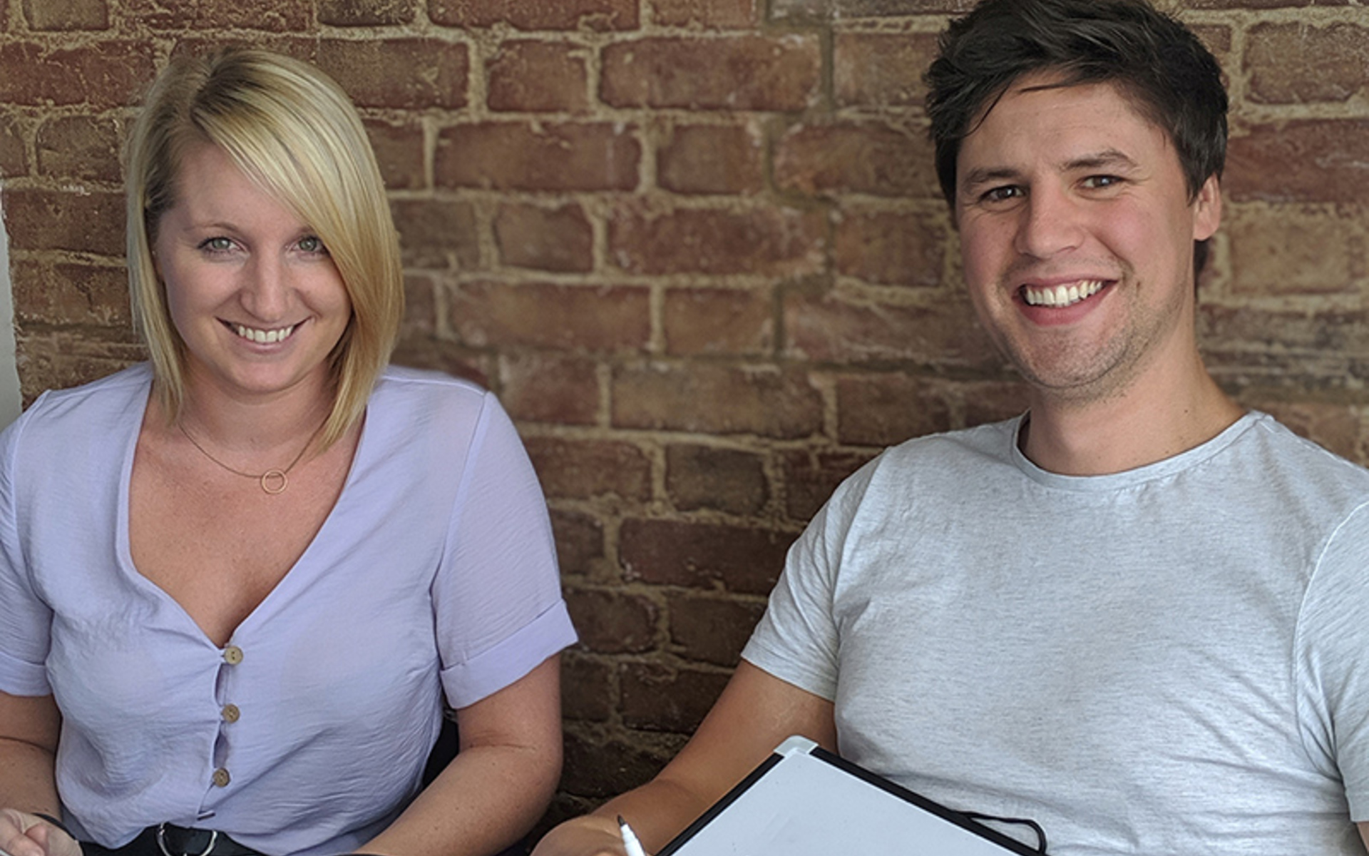 A blonde haired girl and a brown haired man sitting in front of a brick wall smiling
