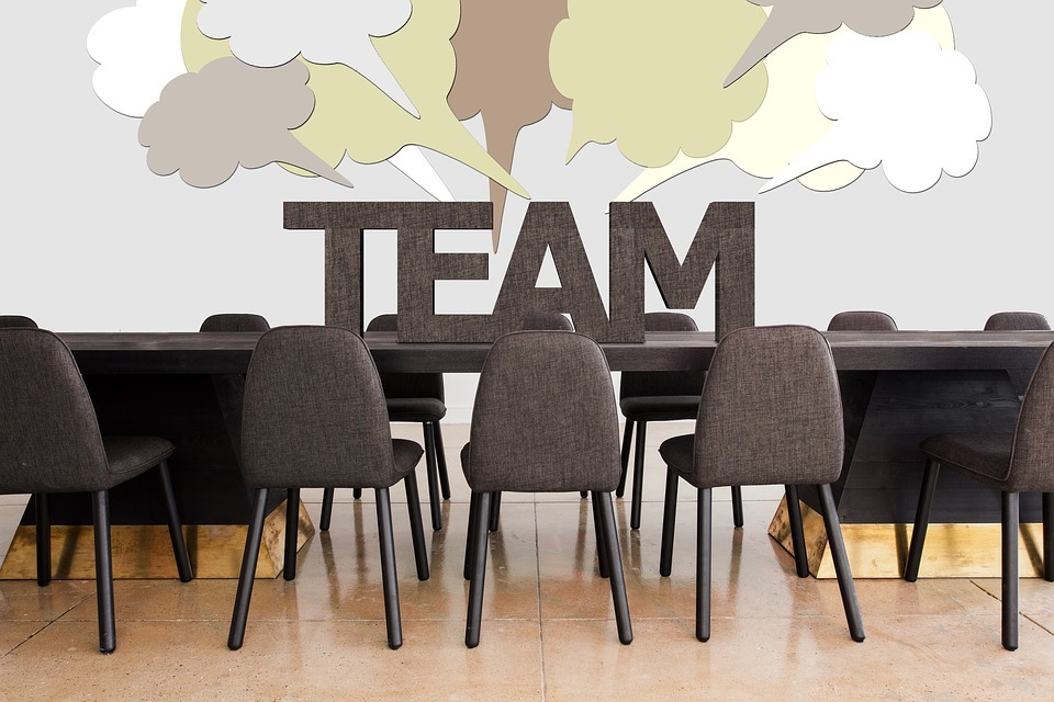 meeting table & chairs with word TEAM on the table and speech bubbles on wall behind